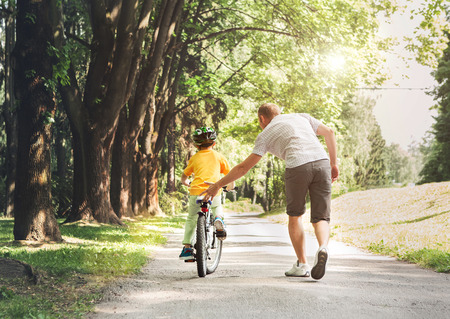 adult care: Father help his son ride a bicycle Stock Photo