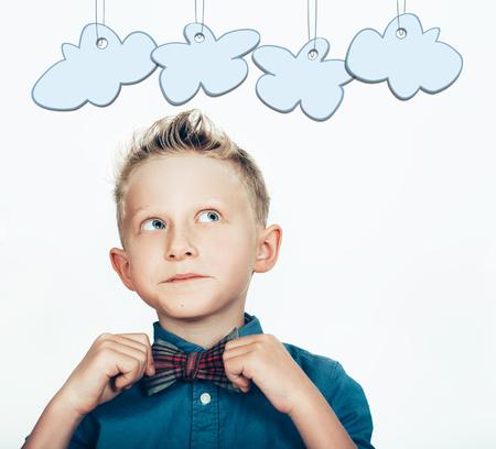 bambini pensierosi: Ragazzino nel papillon con le nubi dei cartoni animati su bianco