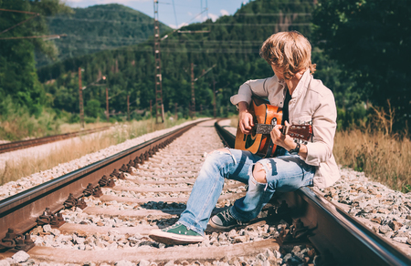 rips: Young man with guitar sitting on the railway Stock Photo