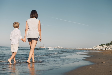 Mother with son walk together on surf sea line Stock Photo