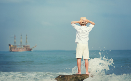 old ship: Boy looking on big old ship on the sea