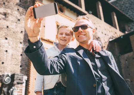 networks: Father with son take a selfie photo in old castle