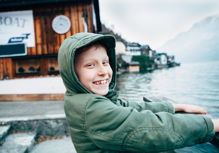 Sincerely smiling boy portrait near the bot pier on mountain lake