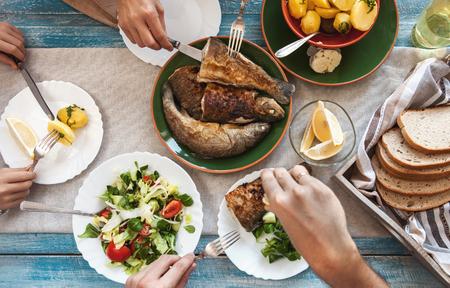 Diner met gebakken vis, aardappelen en verse salade Stockfoto