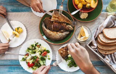 Dinner with fried fish, potatoes and fresh salad