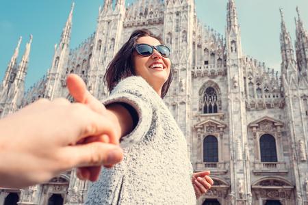 Glimlachende vrouw houdt zijn vriend hand op de Duomo di Milano achtergrond Stockfoto