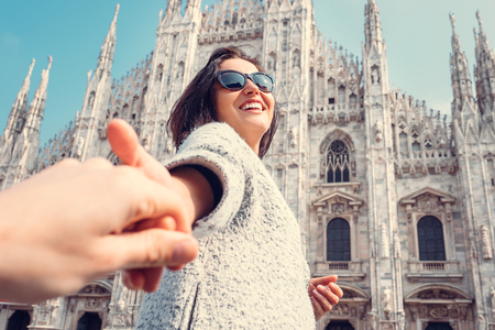 Smiling woman hold his boyfriend hand on Duomo di Milano background