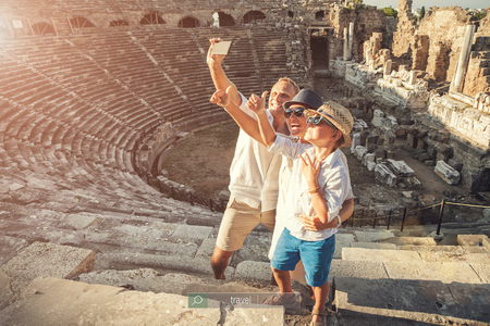 take a history: Young positive family take a self photo on the antique amphithea