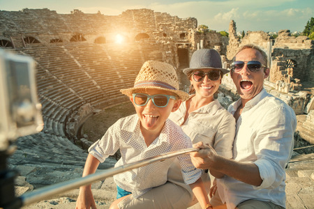 take a history: Young positive famly take a vacation photo on the Side ampitheatre view Stock Photo