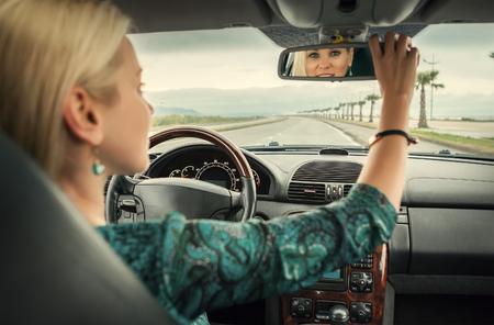 rear view mirror: Woman in car look in rear view mirror