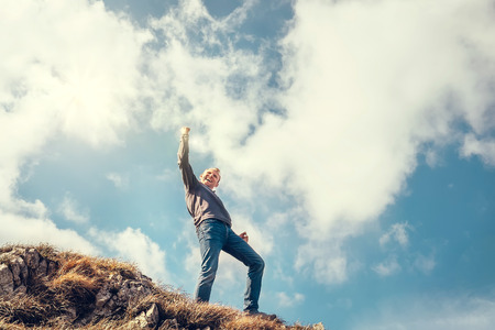 summits: Happy man triumph his climb on the top of mountain Stock Photo