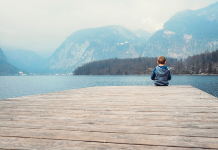 deck: Little boy sits on the wooden pier near the blue mountain lake, Obertraun,Austria