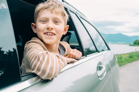 child boy: Happy boy look out from window car