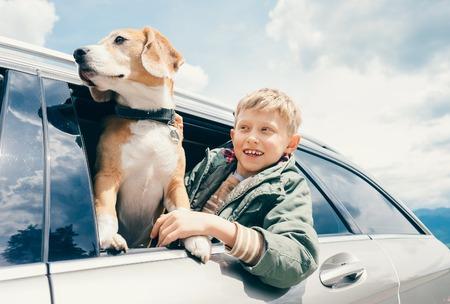 소년과 개가 차 창에서 밖을 내다 본다.