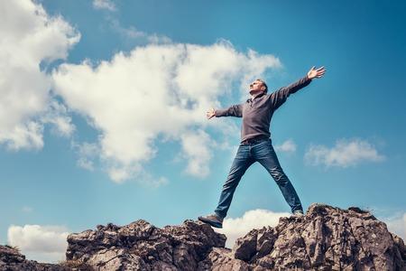 El hombre disfrutar de la libertad se siente en la cima de la montaña Foto de archivo
