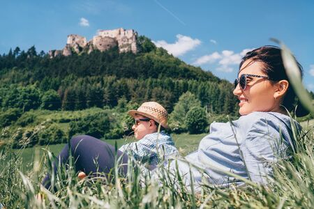 medow: Mother with son rest together on green medow with view on old castle Stock Photo