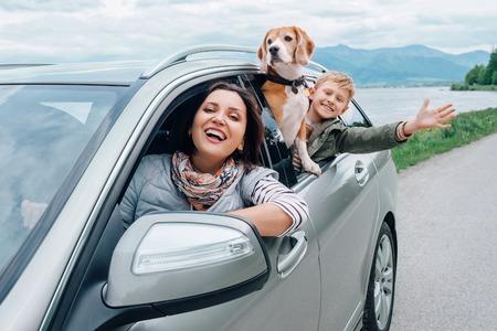 幸せな家族の車の窓から外を見る