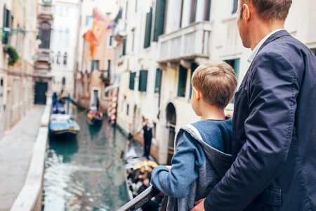Father and son look together on venecian gondolas