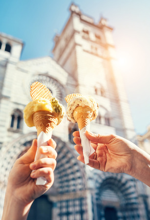 Two hands with ice cream on the San Lorenco Cathedral  background