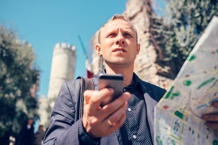 Toeristische man proberen te navigeren zich met kaart en smartphone in onbekende stad