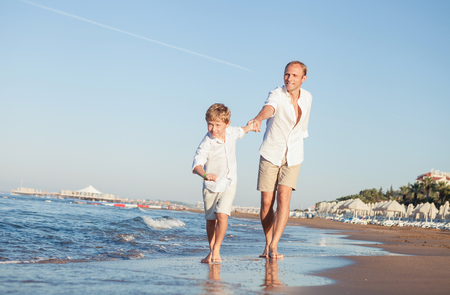 Son with father run together on the sea surfline Stock Photo