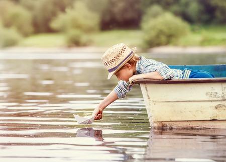 Jongetje lancering papier schip uit oude boot op het meer