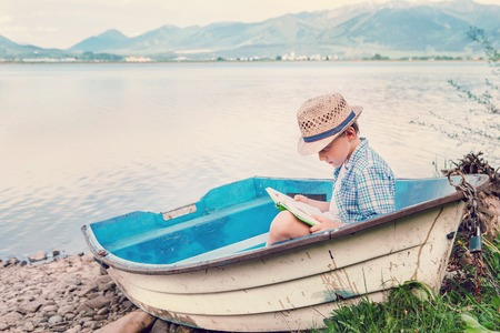 Boy with book seats in old boat on the lake bank Stock Photo