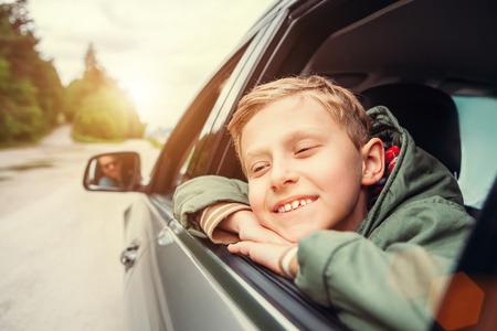niños rubios: Sueño del muchacho mira hacia fuera de la ventana del coche