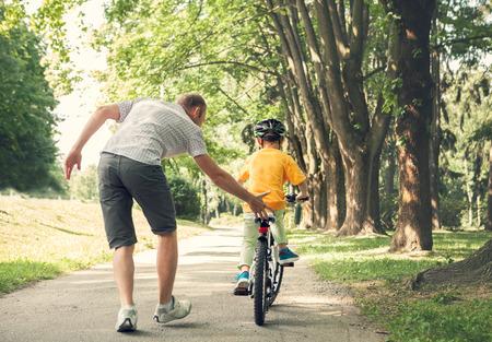 Vater lernen seinen kleinen Sohn, ein Fahrrad zu fahren Standard-Bild - 60090313