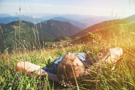 sky and grass: Man lying in high green grass on the mountain medaow Stock Photo