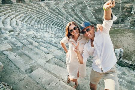 luna de miel: Pares divertidos tomar una foto autofoto en el antiguo anfiteatro en Side, Turquía Foto de archivo