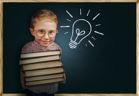 egghead: Boy with books near school chalkboard