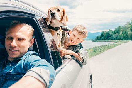 Vader met zoon en hond kijken uit het autoraam