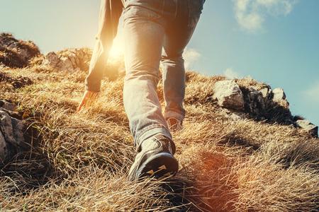 Close-up imade climber benen maken een laatste stap voor de piek Stockfoto