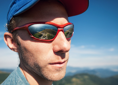 sun glasses: Man in sun glasses with mountain mirorred in it