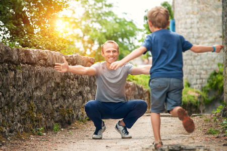Son runs to his father hugs Foto de archivo