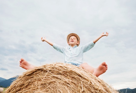 varmint: Happy smiling boy sits astride on the haystack Stock Photo