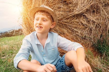 varmint: Boy sits near big haystack on the field
