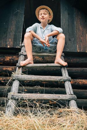 hayloft: Boy sits on the ladder in hayloft