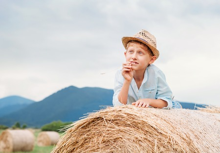 rick: Dreaming boy lying on the rolling haystack Stock Photo