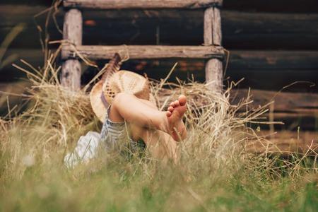 shoeless: Barefoot boy sleeps on the grass near ladder in haystack