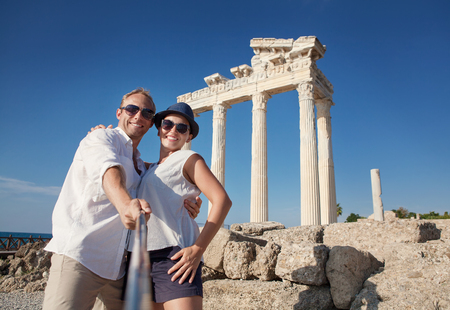 honey moon: Smiling young couple take a selfie photo on antique ruins. Temple of Apollo, Side, Turkey