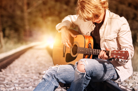 Railway blues. Young man plaing on guitar on the railway Stock Photo