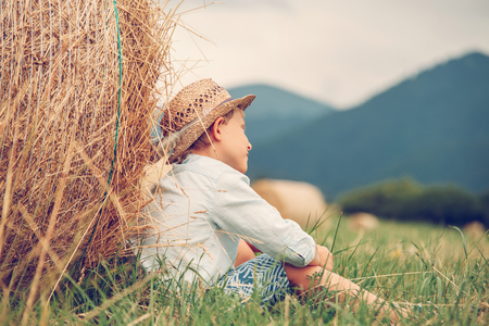 haymaking: Dreaming boy sitting nea the rolling haystack Stock Photo