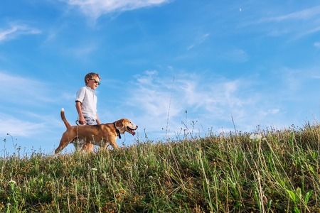 Boy with dog walk together on green hill