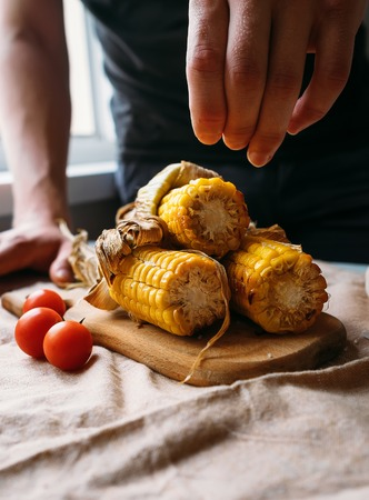 adds: Man adds salt on the roasted corn Stock Photo