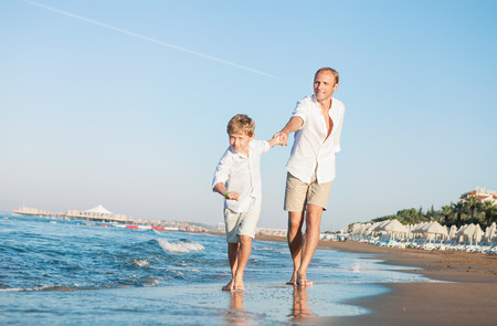 footprints in sand: Son with father run together on the sea surfline Stock Photo