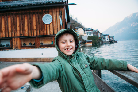sincerely: Sincerely smiling boy near the bot pier on mountain lake