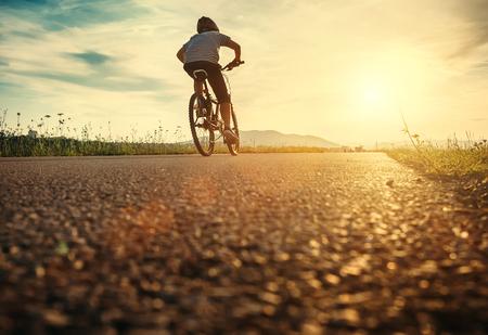 Il ragazzo va in bicicletta alla luce del tramonto