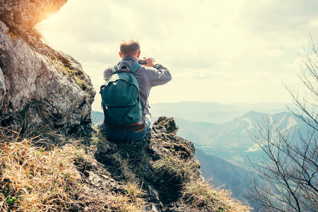 Climber take a mountain landscape photo on his smartphone